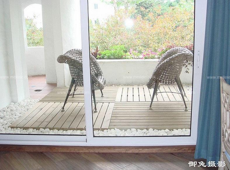 阳台门装修效果图:在东南亚风格阳台装修效果图中,两把木制